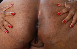 Mature ebony SSBBW Minxx is lying naked on the bed in close-up