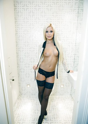 Tanned blonde shows off her vagina and black stockings in the bath