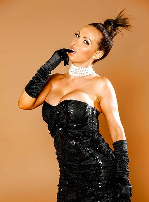 Hot milf Nikki Benz poses in her black dress with a wineglass
