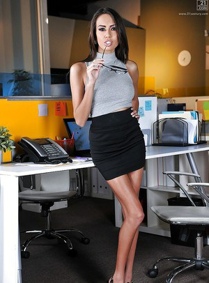 Curvaceous brunette Janice Griffith admires her own long legs and cave