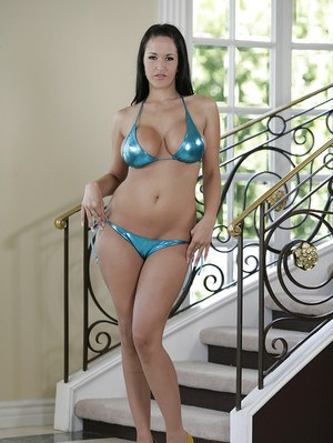 Standing next to a staircase a busty vixen takes off her bikini