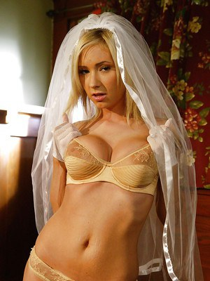 Blonde babe with big tits posing in wedding dress and lingerie