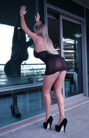 Hot housewife Sandra Otterson posing outdoors in skirt and high heels