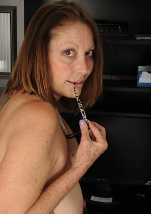 Mature slut Jane McWilliams strips and spreads her pussy in the office