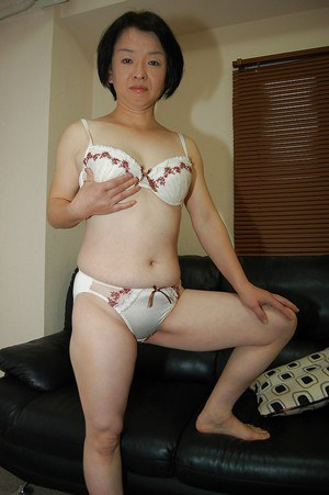 Mature Asian woman Tomoe Nakamachi undresses to reveal tiny tits