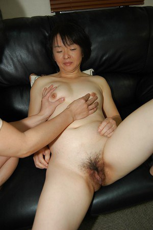 Close ups of Asian woman Tomoe Nakamachi parting her hairy cunt wide