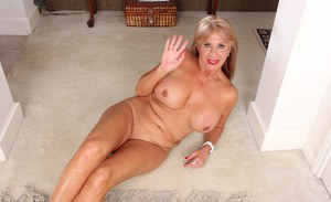 Mature blonde woman Rae Hart posing in brassiere and high heels