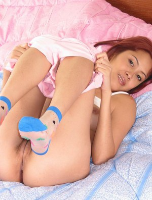Thai hottie toys her hairy cunt while wearing a pair of socks