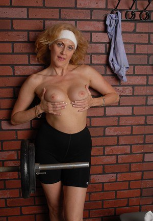 Sporty older dame Dana plays with her big boobs after fitness session