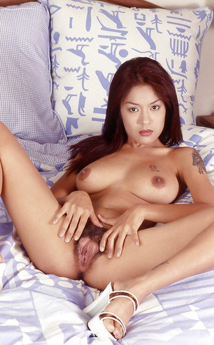 Nude tattooed Thai model opens up her hairy yummy pussy with her hands