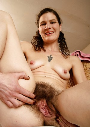 Older brunette woman showing off her hairy armpits and vagina