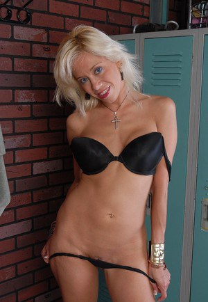 Busty mature blond woman strips off bra and panties exposing bald cunt