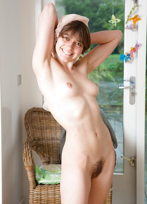Short haired geek girl Flora inserting a finger in her hairy kitty
