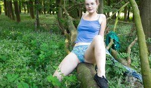 Solo girl in glasses strips naked in woods and masturbates hairy cunt