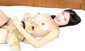 Tiny Asian teen Diep getting naked on her bed and exposing her hairy pussy