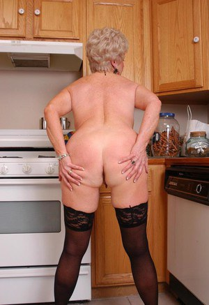 Busty granny Jewel flashes tits and puffy pink pussy in kitchen