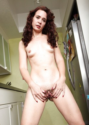 Mature woman Sable Renae flashes her hairy cunt in the kitchen