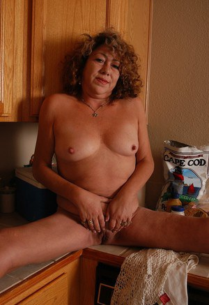 Blonde granny Ivy gets naked in kitchen for shaved pussy fingering