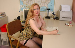 Mature secretary in fishnet stockings lets massive tits loose from bra