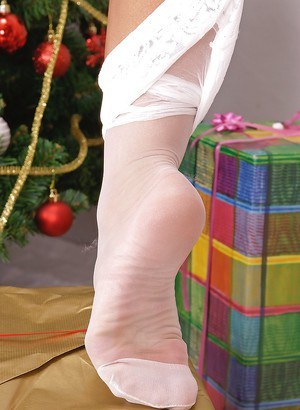 Hot blonde with nice tits in stockings and heels under the Christmas tree