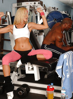 Blonde bodybuilder in pink spandex pants and black panties working out