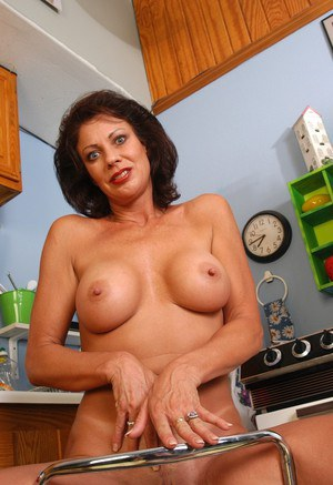 Older brunette lady Vanessa strips naked in kitchen to spread shaved pussy