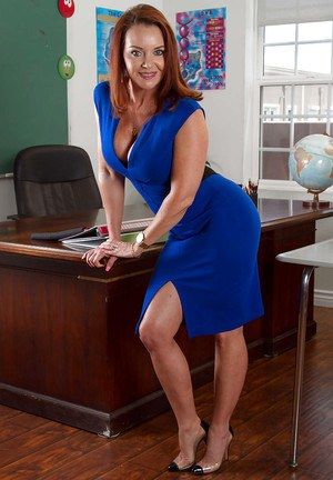 Curvy redhead teacher Janet Mason flashes mature legs in classroom