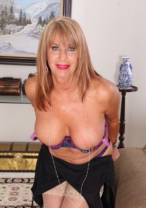 Mature blond in high heels and pantyhose slides panties aside for fingering