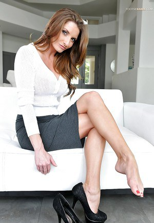 Busty office worker Silvia Saige lets her pretty feet loose from high heels