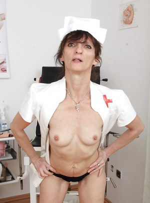 Older nurse Andula poses in uniform before stripping naked and masturbating