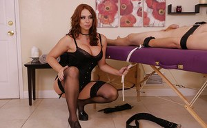 Kinky redhead masseuse ties man to massage table and jerks his cock