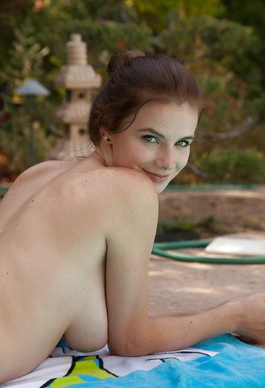 Naturally busty bombshell Essie Halladay posing naked by the pool