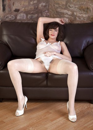 Mature woman in stockings and high heels spreading hairy pussy on couch