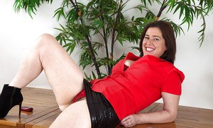 Mature secretary Janey hiking black skirt at work for upskirt panty viewing