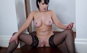 Fully clothed brunette MILF Tanya Cox stripping naked to expose bald pussy