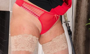Older woman Rae Hart posing fully clothed in white stockings and heels