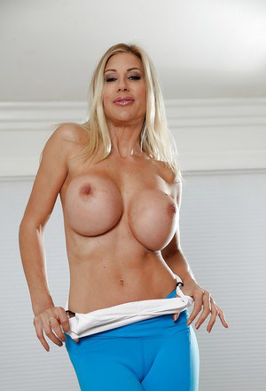 Buxom blonde MILF Puma Swede exposing huge breasts while posing in spandex