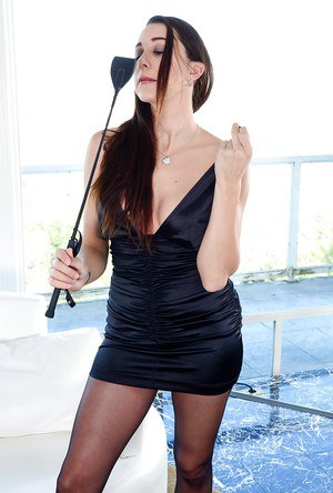 Latina babe model Kaylynn posing fully clothed with riding crop in hand