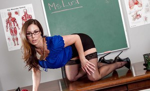 Sultry schoolteacher Kendra Lust posing on desk in black nylons and skirt