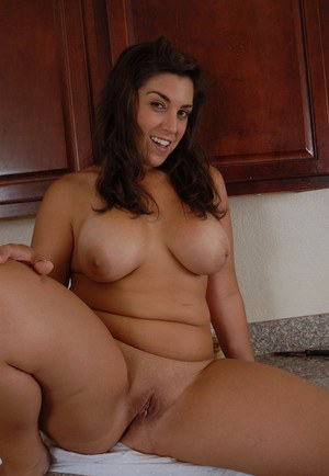 Curvy Latina chick Leigh letting large natural tits loose in kitchen