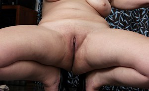Mature lady Sandra Green undresses to expose a shaved vagina