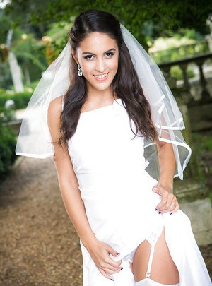 Newly married bride Carolina Abril posing outdoors in wedding dress