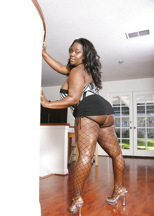 BBBW Kitten Black lifts hefty black juggs while posing in fishnet stockings