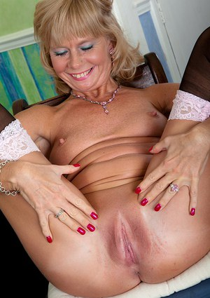 Older blonde broad Cathy Oakley letting nice granny tits loose from corset