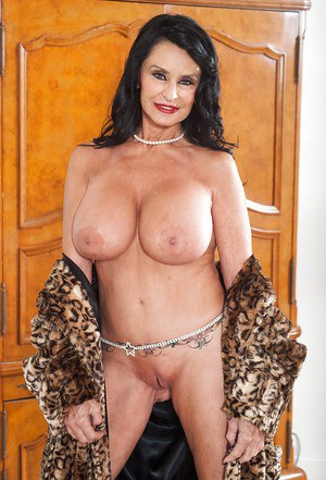 Busty mature pornstar Rita Daniels exposing large tits and shaved cunt