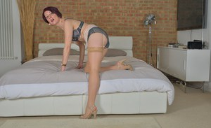 Older Euro broad Penny Brooks posing on bed in heels and hose