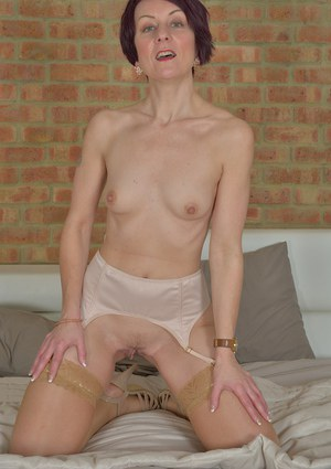 Short haired European dame Penny Brooks exposing small tits and shaved slit