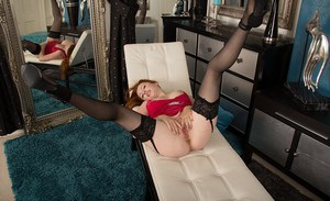 Redheaded MILF Jenny Smith poses in black stockings while parting pussy