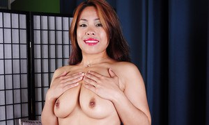 Mature Asian woman Laci Hurst exposing tattoos and shaved vagina