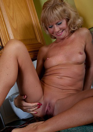Aged blonde lady Cathy Oakley baring her breasts in kitchen
